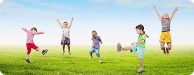 Fem barn i 5-årsåldern som hoppar runt på en gräsmatta