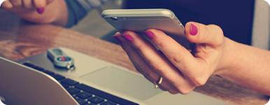Kvinna vid dator med mobil i handen