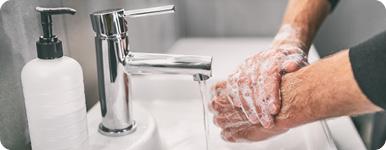 Någon tvättar händer i handfat