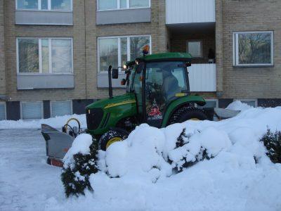 Traktor med snöplog inne på en gård