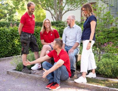Fem kollegor skrattar ihop i parkmiljö