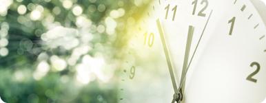 Analog klocka med grönskande bakgrund