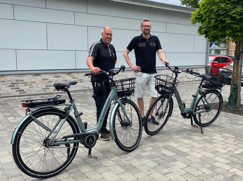 Två män står och håller i styret på två elcyklar.