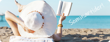 Kvinna med stor solhatt på sandstrand läser en bok