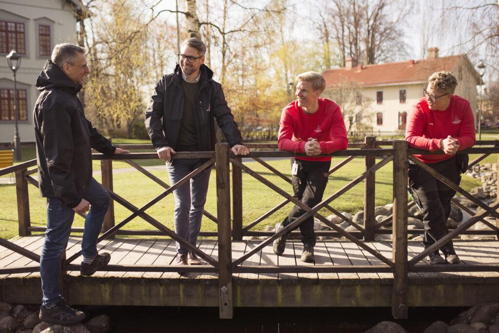 Kollegor står leende på träbro med stadsträdgården i bakgrunden