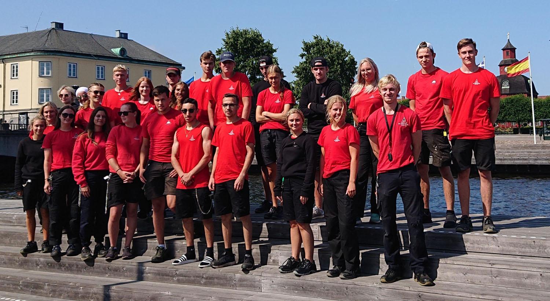 26 ungdomar i röda tröjor står på en trätrappa framför Lidan med Rådhuset i bakgrunden