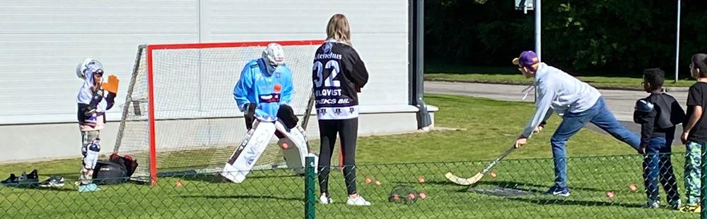 ungdomar skjuter med boll och klubba på bandymålvakt